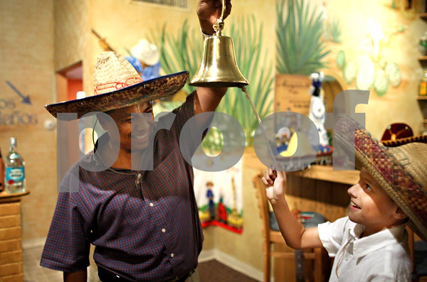 Beck Diefenbach  -  bdiefenbach@daily-chronicle.com<br /> <br /> Jesus Romero shows his son Wyatt, 8, how to ring the bell in celebration of Mexican Independence Day and Mexican Heritage Month at Taxco Restaurant in Sycamore, Ill., on Wednesday Sept. 17, 2009.