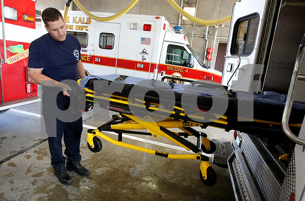 Rob Winner – rwinner@daily-chronicle.com<br /> Lt. Don Faulhaber, of the DeKalb Fire Department, demonstrates how the new Stryker Power-PRO XT ambulance cot operates. The cot utilizes a battery powered hydraulic system that raises and lowers patients with the push of a button. This reduces lifting as well as risk of back injuries.<br /> 07/11/2009