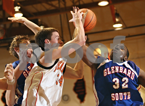 Beck Diefenbach  -  bdiefenbach@daily-chronicle.com<br /> <br /> DeKalb's Grant Olsen (34) tries to stop a shot by Glenbard South's Louis Erkins (32) during the fourth quarter of the game at DeKalb High School in DeKalb, Ill., on Friday Feb. 13, 2009.
