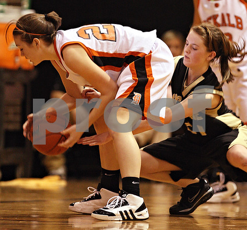 Beck Diefenbach  -  bdiefenbach@daily-chronicle.com<br /> <br /> Sycamore's Kate Binder (21, right) rushes through the legs of DeKalb's Shelby Wood (25) during the fourth quarter of the game at DeKalb High School in DeKalb, Ill., on Tuesday Dec. 1, 2009. Sycamore defeated DeKalb 38 to 33.