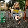 Beck Diefenbach – bdiefenbach@daily-chronicle.com<br /> <br /> Right, Scharlotte Wig (CQ), 3, flies on her family's swing set with a push from her sister Rylynne (CQ) between rain storms at their Sycamore home on Friday June 19, 2009.