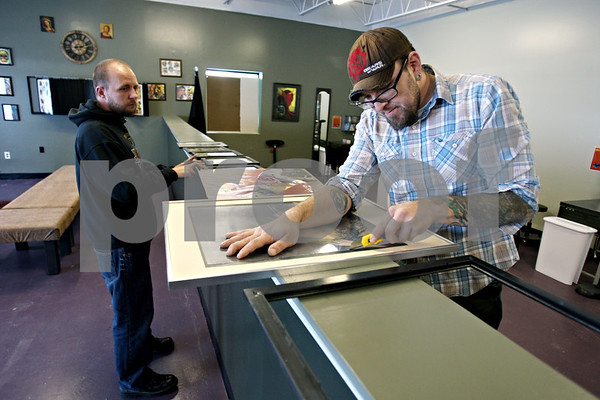 Rob Winner – rwinner@daily-chronicle.com<br /> On Friday December 11, 2009, Jon Bowman (left) and Chris May, owners of Proton Tattoo Shop in DeKalb, finish up preparing their business for their grand opening in DeKalb, ILL.