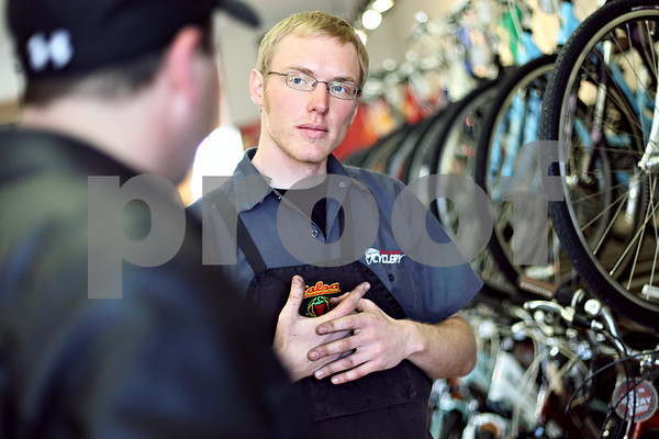 """Beck Diefenbach  -  bdiefenbach@daily-chronicle.com<br /> <br /> Bike mechanic Russ Stewart listens to Craig French, of Plano, explains what type of bike he is interested in at North Central Cyclery in DeKalb, Ill., on Thursday March 27, 2009. """"People are looking for an alternative, for saving money and exercise,"""" said store owner Tobie DePauw. """""""