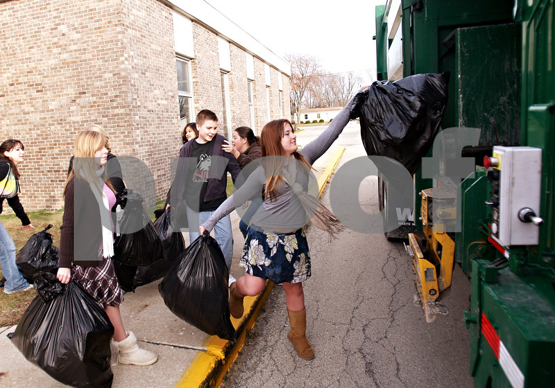 Beck Diefenbach  -  bdiefenbach@daily-chronicle.com<br /> <br /> Ecobuds Club member, and DeKalb High School sophomore, Alissa Whitt (center) tosses bags of plastic recyclables which sat on display in front of the school in DeKalb, Ill., on Thursday Nov. 12, 2009. Ecobuds is a student environmental group, which organized the collection of recyclables and presentation so that students and community members would notice the importance of using a recycling bin instead of a trash can.