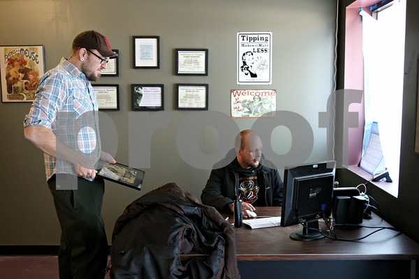Rob Winner – rwinner@daily-chronicle.com<br /> On Friday December 11, 2009, Chris May (left) and Jon Bowman, owners of Proton Tattoo Shop in DeKalb, finish up preparing their business for their grand opening in DeKalb, ILL.