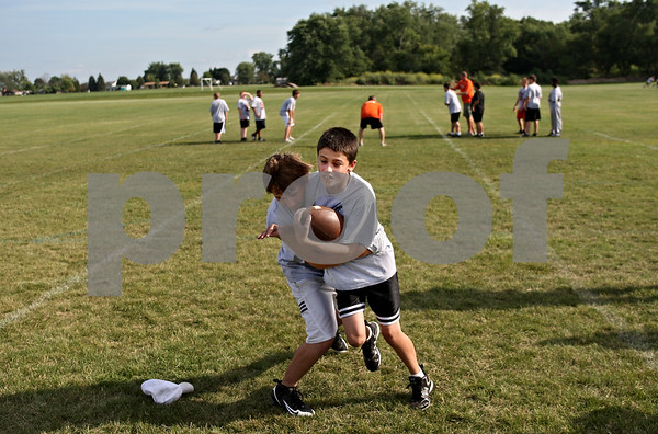 Beck Diefenbach  -  bdiefenbach@daily-chronicle.com<br /> <br /> Huntley's Jonathan Snow, left, and Troy West practice angled tackles during a junior high football camp hosted by DeKalb High School in DeKalb, Ill., on Wednesday July 29, 2009.