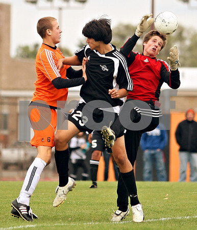 Beck Diefenbach  -  bdiefenbach@daily-chronicle.com<br /> <br /> Kaneland's Alex Dorado (23) blocks DeKalb's Chris Calbow (6) as Kaneland goal keeper XXXX (right) leaps for the ball during the first half of the game at DeKalb High School in DeKalb, Ill., on Monday Sept. 28, 2009.