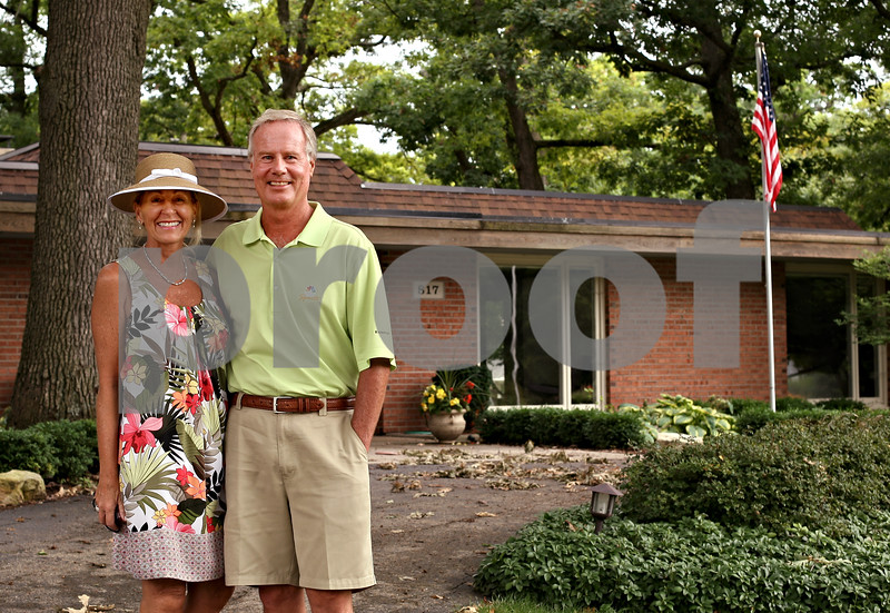 Beck Diefenbach  -  bdiefenbach@daily-chronicle.com<br /> <br /> DeKalb native and NBC Sports golf analyst Mark Rolfing, right, and his wife Debi in front of his childhood home on Lawnwood Avenue in DeKalb, Ill., on Tuesday Aug. 17, 2009. Rolfing lived in the house when his father died in a plane crash on Nov. 29, 1960. Rolfing will be announcing at this week's Solheim Cup.