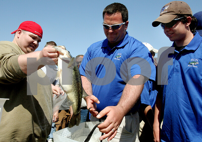 Rob Winner – rwinner@kcchronicle.com<br /> Jason Huddleston (from left) weighs in a large mouth bass caught by the St. Charles North team including coach Tim Pinks and junior Derrick Hoffman during Friday's IHSA fishing sectional at Shabbona Lake on Friday. The fish, which was caught by Hoffman, weighed in at 4.107.<br /> 04/24/2009
