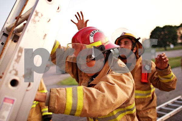 Beck Diefenbach  -  bdiefenbach@daily-chronicle.com<br /> <br /> Kaneville Fire Protection District cadet Jason Warren (center) practices raising a ladder as he is shadowed by firefighter Jesse Sanchez during drills at Kaneland High School in Maple Park, Ill., on Tuesday August 11, 2009.