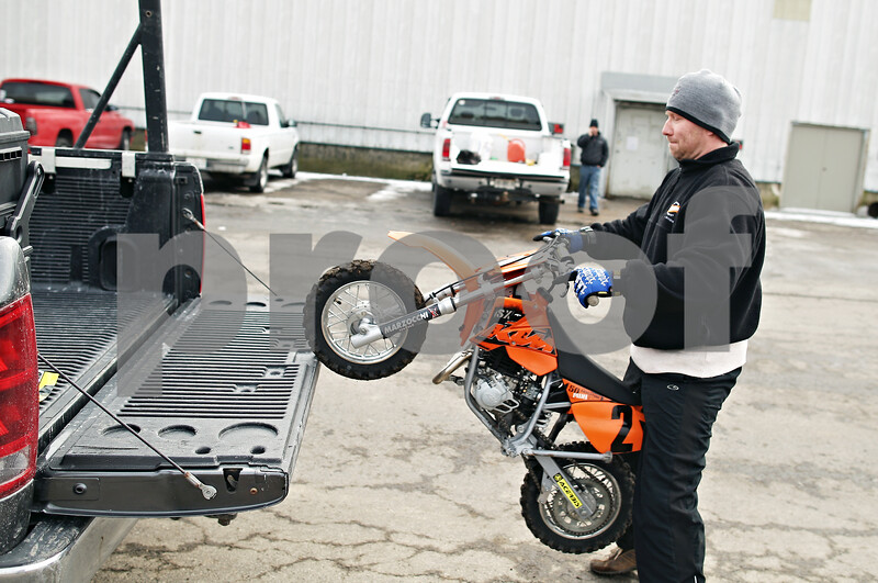 """Beck Diefenbach  -  bdiefenbach@daily-chronicle.com<br /> <br /> Radko Tomko, of Elgin, lift's his 5 year old son's motor cross motorcycle into the back of his truck after riding at Waterman International Raceway in Waterman, Ill., on Tuesday Feb. 17, 2009. Tomko believes that an exception should be made for motorcross in respect to the new lead laws. """"The kids are the future of this sport,"""" Tomko said."""