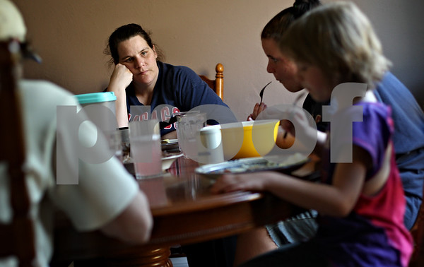 Beck Diefenbach  -  bdiefenbach@daily-chronicle.com<br /> <br /> Debra Edwards watches two of her daughters, Faith, 16, (back) and Jada, 7, eat dinner in their DeKalb home on Thursday May 21, 2009.
