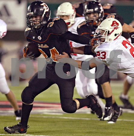Beck Diefenbach  -  bdiefenbach@daily-chronicle.com<br /> <br /> DeKalb running back Dalton Watie (34) slips through the hands of Ottawa's Taylor Ostrowski (23) during the first quarter of the game at Huskie Stadium of Northern Illinois University in DeKalb, Ill., on Friday Aug. 28, 2009.