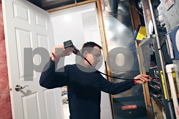 Beck Diefenbach  -  bdiefenbach@daily-chronicle.com<br /> <br /> Ron Breese, of Breezy's Heating and Air Conditioning, uses a camera on a cord to check for obstructions or leaks in the heating system as part of a preseason clean and check of a home in DeKalb, Ill., on Monday Feb. 9, 2009.