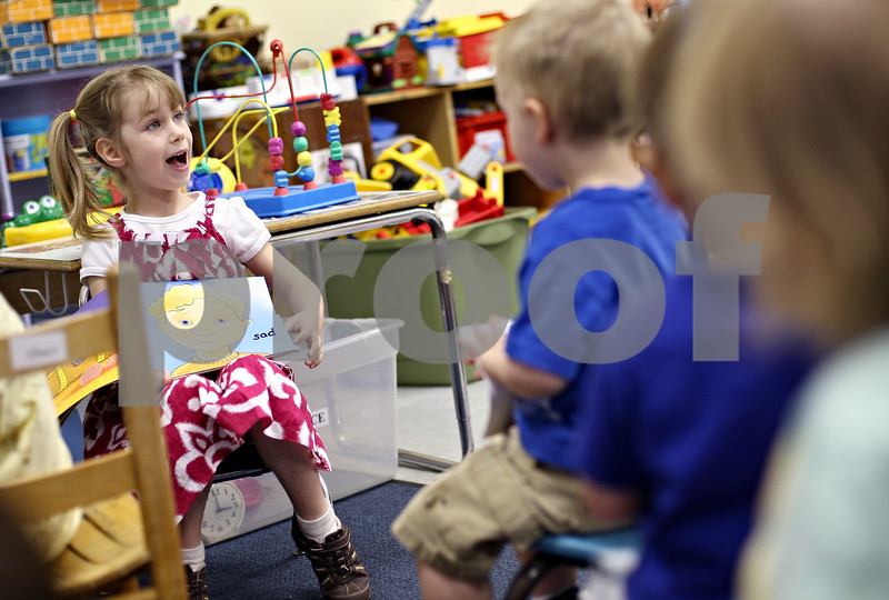 Beck Diefenbach  -  bdiefenbach@daily-chronicle.com<br /> <br /> Lillian Duerkes, 5, reads a book to a group of 2 year olds as part of a reading program at The Growing Place in DeKalb, Ill., on Friday June 5, 2009.