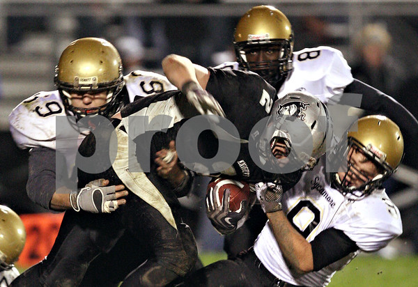 Beck Diefenbach  -  bdiefenbach@daily-chronicle.com<br /> <br /> Kaneland wide receiver Blake Serpa (2, center) is taken down by Sycamore defensive lineman Dorian Hryniewicki (69, left) and defensive back Tommy Nice (9, right) during the fourth quarter of the class 5A playoff game at Kaneland High School in Maple Park, Ill., on Saturday Oct. 31, 2009.