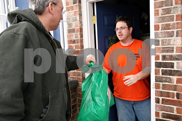 Rob Winner – rwinner@daily-chronicle.com<br /> As a volunteer for Goodfellows, Bill Scholl (left), of Clare, delivers a bag full of gifts to the home of Jon Hash, of Sycamore, Ill., on Thursday December 24, 2009. Goodfellows is a volunteer group that delivers gifts to the needy during the holidays.