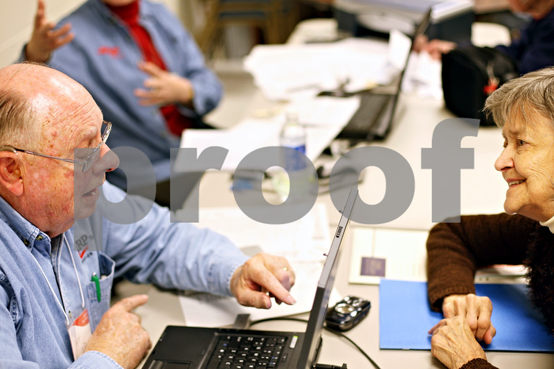 Beck Diefenbach  -  bdiefenbach@daily-chronicle.com<br /> <br /> AARP volunteer David Wood, left, explains the tax returns to Hilkka Itkonen (CQ), of DeKalb, on the last day of the AARP free tax assistance for seniors at the Senior Services Center in DeKalb, Ill., on Tuesday April 14, 2009.