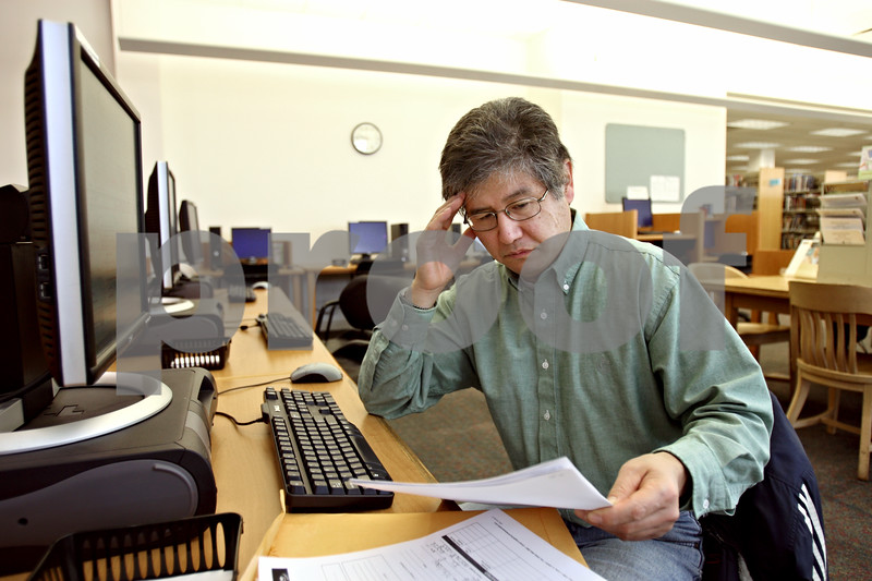 Rob Winner – rwinner@daily-chronicle.com<br /> Tony Virtue, of Sycamore, looks over a packet of job training information for a waste water treatment operator at the Sycamore Public Library in Sycamore, Ill. on Wednesday December 16, 2009. Virtue spends about an hour and a half every weekday at the library searching for employment.