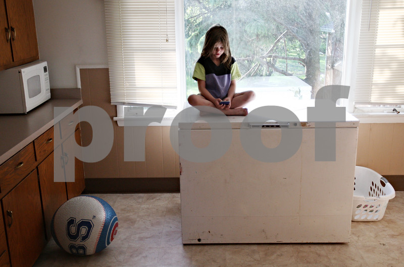 Beck Diefenbach  -  bdiefenbach@daily-chronicle.com<br /> <br /> Jina Edwards, 7, plays with a calculator while sitting on a freezer in the kitchen of her family's DeKalb home on Thursday May 21, 2009.