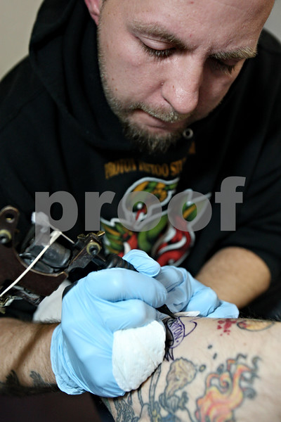 Rob Winner – rwinner@kcchronicle.com<br /> Jon Bowman tattoos the leg of co-owner Chris May at Proton Tattoo Studio on in DeKalb, Ill. on Saturday December 19, 2009 for the shop's first tattoo ever.
