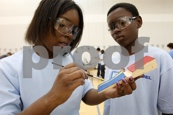 Rob Winner – rwinner@daily-chronicle.com<br /> <br /> Rashida Cooper, a student at NIU, and her son Tylian, 13, work together building and painting a derby car on Saturday afternoon.<br /> <br /> 10/10/2009