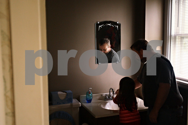 Beck Diefenbach  -  bdiefenbach@daily-chronicle.com<br /> <br /> John Hadley, right, helps his daughter Morgan, 4, wash her hands before dinner in their new home in DeKalb, Ill., on Friday Oct. 2, 2009.