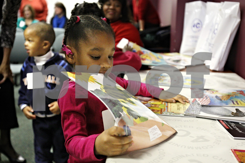 Rob Winner – rwinner@daily-chronicle.com<br /> Mia Adeoti, 4, looks through a pile of donated books at the Community Coordinated Child Care office on Tuesday morning in DeKalb.<br /> 11/17/2009