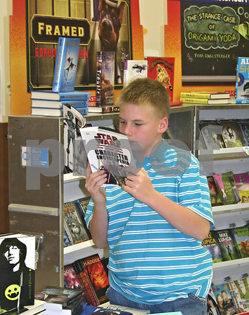 Dana Herra dherra@daily-chronicle.com<br /> <br /> John Hermes, 12, reads a book he picked up off the shelf at Camelot School's first ever book fair on Friday. The book fair continues through Tuesday.
