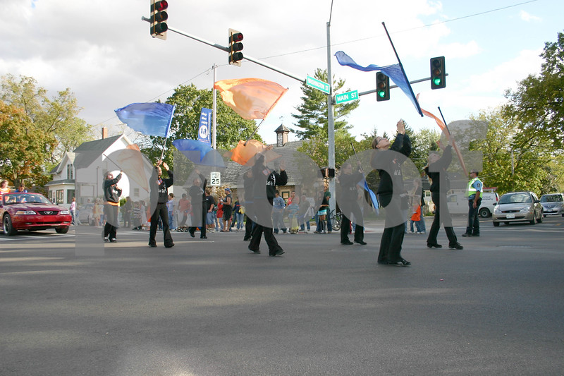 By Nicole Weskerna, nweskerna@daily-chronicle.com<br /> <br /> The Genoa-Kingston flag team marches down Main Street in Genoa Friday during the homecoming parade before the Genoa Cogs football team takes on the Oregon Hawks later that evening.