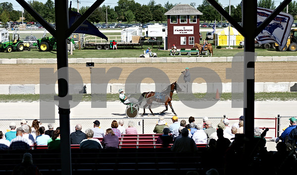 Rob Winner  -  rwinner@daily-chronicle.com<br /> <br /> Spectators of the harness race at the Sandwich Fair on Wednesday September 9, 2010 watch as a driver and his horse pass by the grandstand before the start of the last race in Sandwich, Ill.