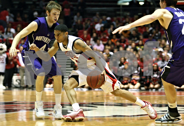 Rob Winner – rwinner@daily-chronicle.com<br /> <br /> NIU forward Bryan Hall (center) moves the ball past Northwestern guard Alex Marcotullio in the first half of their game in DeKalb, Ill. on Friday November 12, 2010.