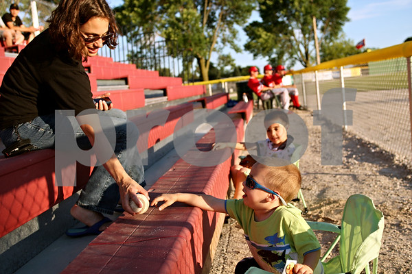 Beck Diefenbach  -  bdiefenbach@daily-chronicle.com<br /> <br /> Jamie Wilkerson, left, of Sycamore, plays with her sons Bruno, 3, (front) and Jordan, 6, (back) while sitting in the new seats behind left field at Founders Field during the DeKalb County Liners home opening game at Sycamore Park in Sycamore, Ill., on Wednesday June 16, 2010.