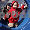 Rob Winner – rwinner@daily-chronicle.com<br /> <br /> Brody Gillies, 1 of DeKalb, crawls through a tunnel at the Hopkins Park playground as child care provider Kellie Sosa, of Malta, follows close behind on Friday March 26, 2010 in DeKalb, Ill.