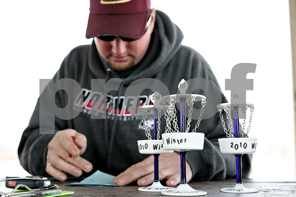 "Rob Winner – rwinner@daily-chronicle.com<br /> <br /> DeKalb County Disc Golf Club member Jason Gordon, of DeKalb, fills out a scorecard at Pioneer Park in Kirkland, Ill. on Saturday March 27, 2010. On Saturday, the club recognized outstanding members of their winter league, which ran from November to March, with ""thropies,"" made by Gordon who is also a glassblower at Northern Illinois University. The club's summer league begins April 2 and will meet every Friday at 5 p.m. For more information visit  <a href=""http://www.dcdisc.ning.com"">http://www.dcdisc.ning.com</a>."
