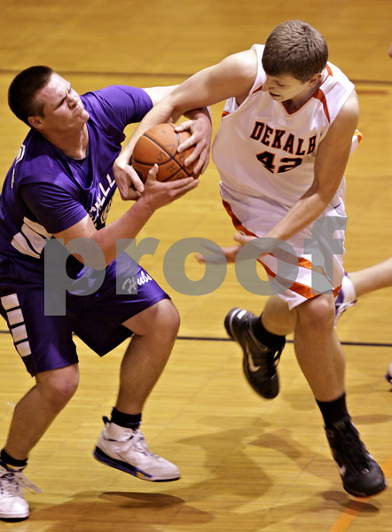 Beck Diefenbach  -  bdiefenbach@daily-chronicle.com<br /> <br /> Dekalb's Jordan Threloff (42) rips the ball from Rochelle's Micah McCulloch (44) during the first quarter of the game at DeKalb High School  in DeKalb, Ill., on Friday Jan. 8, 2010.