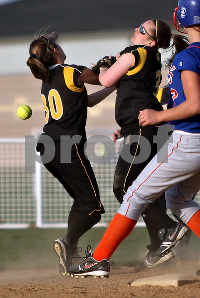 Beck Diefenbach  -  bdiefenbach@daily-chronicle.com<br /> <br /> Sycamore's Anna Buzzard (30, left) and Becca Schroeder (3, center) collide and miss the pop fly during the top of the seventh inning of the game against Genoa-Kingston at Sycamore High School in Sycamore, Ill., on Thursday April 1, 2010. G-K defeated Sycamore 9 to 2.
