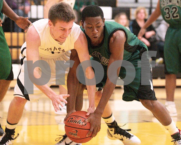 Kyle Bursaw – kbursaw@daily-chronicle.com<br /> <br /> Sycamore's John Copple and Catamount's Jason Williams both fight for the ball. The Sycamore Spartans defeated the Gary Comer College Prep Catamounts  51-48 during the Leland G. Strombom Tournament on Friday, Nov. 26, 2010