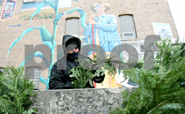 Rob Winner – rwinner@daily-chronicle.com<br /> <br /> Bundled from head to toe, Steve Knutzen of the DeKalb Park District decorates Memorial Park with evergreen garland in downtown DeKalb on Wednesday afternoon.
