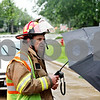 Beck Diefenbach  -  bdiefenbach@daily-chronicle.com<br /> <br /> Sycamore's Lt. Jack Sparkz talks with local residents as the West State Street is blocked off to traffic following a downed power line in Sycamore, Ill., on Friday June 18, 2010.