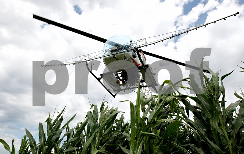 Rob Winner – rwinner@daily-chronicle.com<br /> <br /> A helicopter piloted by Ron Smith, of Hendrickson Flying Service located in Rochelle, prepares to land while spraying farm fields near Fenstermaker and Barber Greene roads in Cortland Township on Friday July 23, 2010.