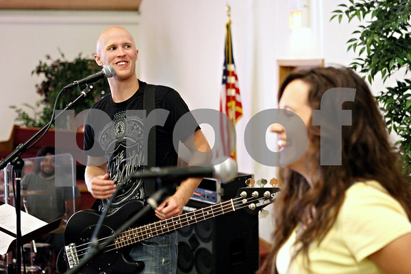 Rob Winner – rwinner@daily-chronicle.com<br /> <br /> Bassist Nate Miller (left) of the musical group Elevate shares a laugh with fellow band members including Sarah Mikan during band practice at First Baptist Church of Sycamore in Sycamore, Ill. on Saturday September 11, 2010. Elevate will be performing at Saturday's Praizapalooza event at Hopkins Park in DeKalb.