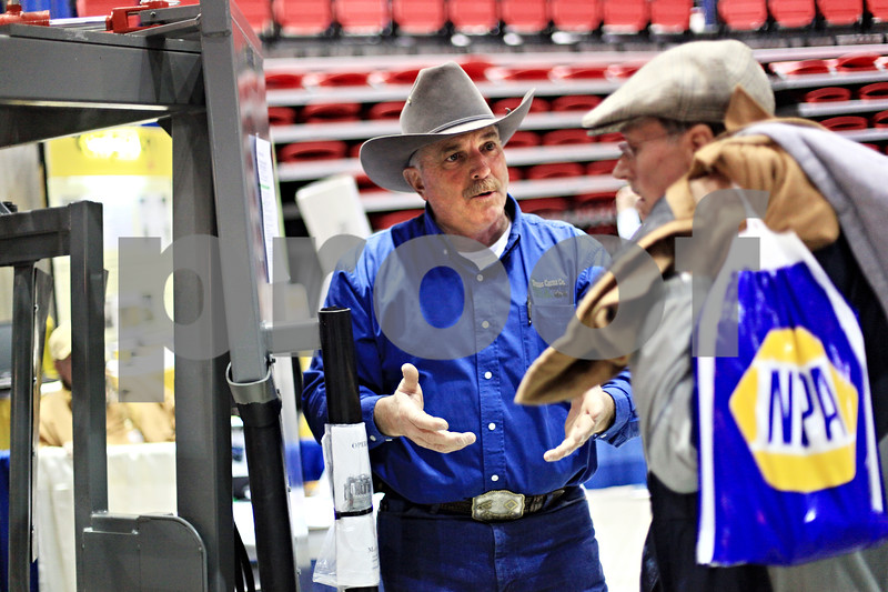 Beck Diefenbach  -  bdiefenbach@daily-chronicle.com<br /> <br /> Don Burks (center), of Dubas Cattle Company, explains the the hydraulic livestock squeeze shoot to Larry Larson, a cream farmer in Sycamore, at the Northern Illinois Farm Show at the Northern Illinois University Convocation Center in DeKalb, Ill., on Wednesday Jan. 6, 2009.