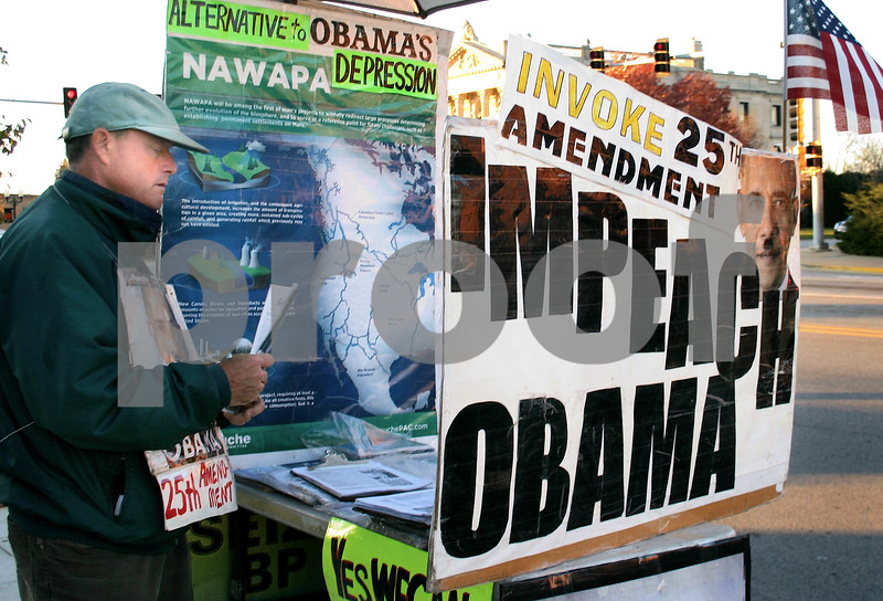 Caitlin Mullen - cmullen@daily-chronicle.com <br /> <br /> Don Clark, an organizer with the non-partisan LaRouche Political Action Committee, stands Wednesday outside the Sycamore Post Office downtown providing information about the group's goal to impeach President Barack Obama. Clark and his wife Judy offered fliers to those interested. 11/03/10