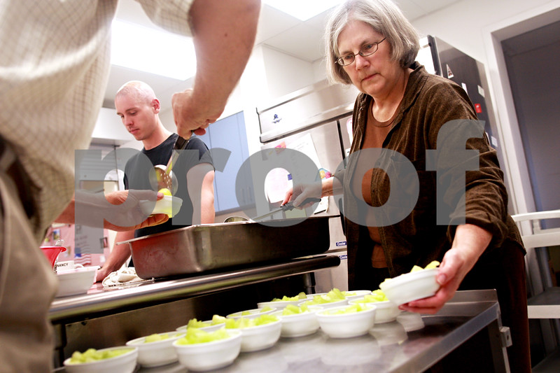 Beck Diefenbach  -  bdiefenbach@daily-chronicle.com<br /> <br /> Volunteer Maylan Dunn-Kenney places bowls of melon on a cart for the free community dinner at the VAC lunch room in the Elder Care Center in DeKalb, Ill., on Wednesday July 7, 2010.