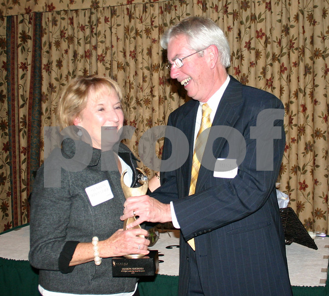 Sharon Rhoades receives a trophy from Athena Award co-sponsor Mike Mooney Thursday after being selected from nine other nominees as recipient of the 2010 Athena Award.<br /> <br /> By NICOLE WESKERNA nweskerna@daily-chronicle.com
