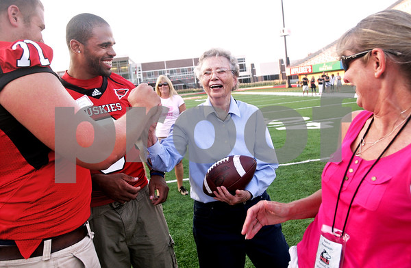Beck Diefenbach  -  bdiefenbach@daily-chronicle.com<br /> <br /> Mary Bell (center), of DeKalb, gets a high five from Scott Wedige (far left) and DeMarcus Grady during the Northern Illinois University football 101 women's clinic at Huskie Stadium in DeKalb, Ill., on Tuesday July 27, 2010.