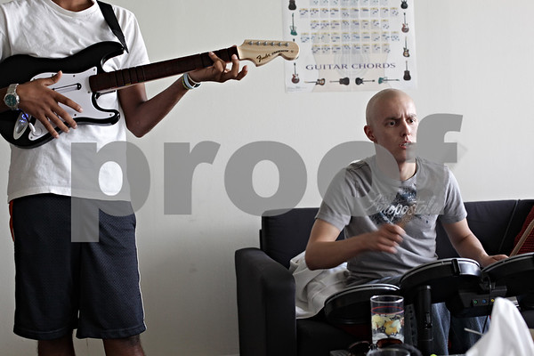 Beck Diefenbach – bdiefenbach@daily-chronicle.com<br /> <br /> Kevin, right, plays video games with his brother Keerti, left, at an apartment the family rented near the hospital in Chicago, Ill., on July 18, 2009. Despite checking out of the hospital, Kevin has to return for check-ups multiple times a week. The family rented an apartment near the hospital so not to have to commute from DeKalb.