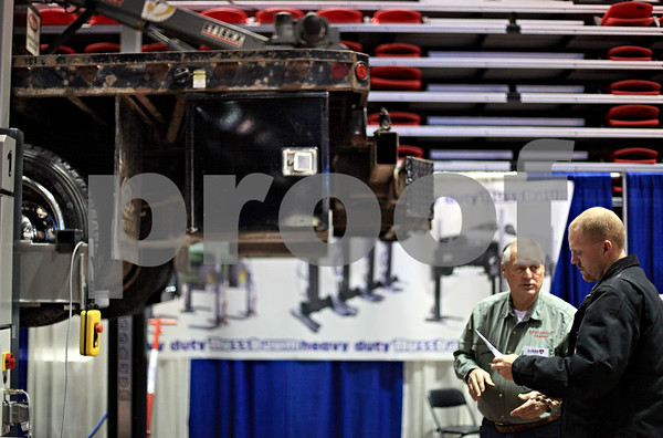 Beck Diefenbach  -  bdiefenbach@daily-chronicle.com<br /> <br /> Ryan Kohl (far right), of Soil Service Inc., listens to Bob Chestain, of Indiana Auto Motive Equipment explain the abilities of a mobile column car lift as a large truck hovers next to them at the Northern Illinois Farm Show at the Northern Illinois University Convocation Center in DeKalb, Ill., on Wednesday Jan. 6, 2009.