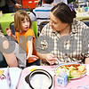 Beck Diefenbach  -  bdiefenbach@daily-chronicle.com<br /> <br /> Volunteer Erin Templin (left), 6, serves Ellen Hannig, of DeKalb, a cup of peaches during the biweekly VAC community dinner at the Senior Services Center in DeKalb, Ill., on Wednesday March 31, 2010.
